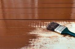 Malen eines Holztischs unter Verwendung des Malerpinsels Lizenzfreie Stockfotos