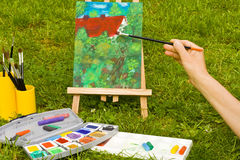 Malen, painting. Malen mit Farbe, Pinsel, Leinwand im Garten, colours, painting with brushes, canvas in a garden Royalty Free Stock Photos