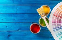 Malen Sie Dosenfarbpalette, die Dosen, die mit Bürsten auf blauer Tabelle geöffnet sind stockfotos