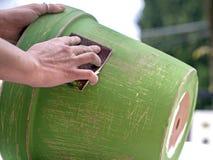 Malen Sie Tongefäß und benutzen Sie Sandpapier, um es zu verzieren Stockfotografie