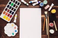 Malen Sie Versorgungen und leeres Papier Stockfoto