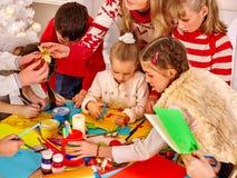 Malende Kinder und geschnittenes sissors Papier an der Kunst Stockbild
