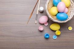 Malende Ostereier mit Bürsten und Farbe auf hölzernem Hintergrund stockfotos