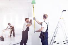 Malendes weißes Wandgrün des Handwerkers bei der Fertigung des Innenraums lizenzfreie stockfotografie