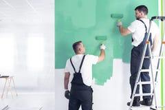 Maler auf der Leiter, die ein Wandgrün beim Neu streichen Inter- malt stockfotos