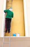 Maler auf einer Leiter, welche die Wand malt stockfoto