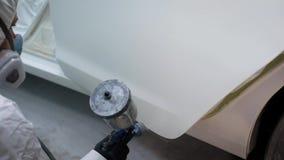 Maler bedeckt Automobiltür in der weißen Farbe, setzt sich hin und benutzt industrielle Farbspritzpistole, Nahaufnahme stock footage