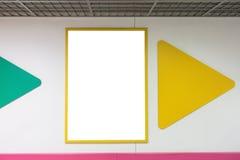 Maler den övre tomma affischramen för åtlöje med gula ramar som hänger på väggen i shopping Royaltyfria Foton
