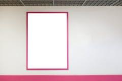 Maler den övre tomma affischramen för åtlöje med rosa ramar som hänger på väggen i shopping Arkivbilder