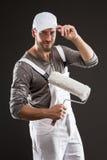 Maler in den weißen Jeansstoffen und im Hut, die mit Farbenrolle steht Stockbild