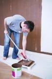 Maler, der eine Lackrolle verwendet Stockbild