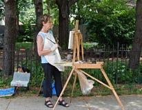 Maler, der ihre Arbeit studiert Stockfotografie