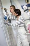 Maler der jungen Frau in Berufsausbildung woth Lehrer stockbild