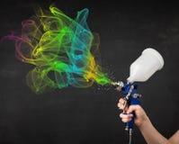 Maler, der mit Spritzpistole und bunter Farbe der Farben arbeitet Stockbild