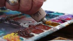 Maler drückt Farbe von einem Rohr zusammen stock video