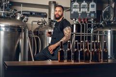 Maler farpado preto que apresenta a cerveja do ofício no microbrewery imagem de stock