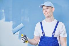 Maler gegen blaue Wand stockbild