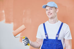 Maler gegen orange Wand lizenzfreie stockbilder