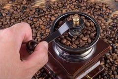 Maler grillade malande kaffe för den manliga handen i gammalt retro kaffe och kaffebönor i bakgrund Arkivfoton