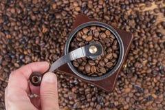 Maler grillade malande kaffebönor för manlig hand i gammalt retro kaffe och kaffebönor i bakgrund Royaltyfri Foto