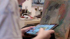 Maler In Her Shop, das ein Digital-Tablet verwendet, um das Netz zu surfen stock video footage