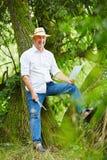Maler im Sommer, der auf einem Baum sich lehnt Lizenzfreies Stockbild
