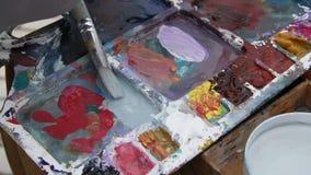 Maler mischt Farbe auf der Palette stock footage