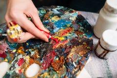 Maler mischt Farbe auf der Palette nahaufnahme Stockbilder