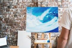 Maler steht vor dem Gestell mit einem Segeltuch und betrachtet seine Arbeit stockbilder