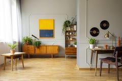 Malerei auf grauer Wand über hölzernem Schrank im Arbeitsplatzinnenraum mit Stuhl am Schreibtisch Reales Foto stockbild