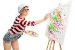 Malerei der jungen Frau auf einem Segeltuch Stockfotografie