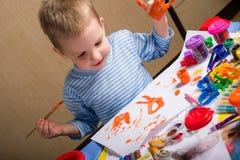 Malerei des kleinen Jungen Stockfotos