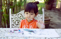 Malerei des kleinen Mädchens mit Malerpinsel- und Wasserfarben Stockbild