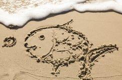Malerei eines Fisches im Sand Stockfotos