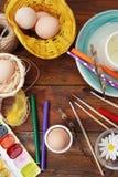 Malerei-Ostereier mit Bruses, Bleistiften und Farben Flache Lage Beschneidungspfad eingeschlossen Dunkler hölzerner Hintergrund V Lizenzfreie Stockbilder