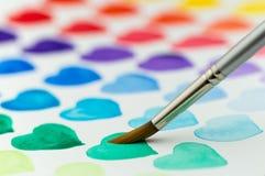 Malereiaquarellherzen mit einem Malerpinsel Flache Schärfentiefe Stockfotografie