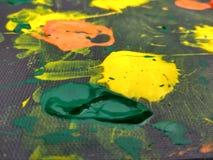 Malereistellen auf schwarzem Hintergrund mit gelber, orange und grüner Farbe Stockbild