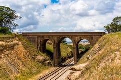 Malerische alte Bogenbrücke, Viadukt mit Eisenbahn darunterliegend Lizenzfreie Stockbilder