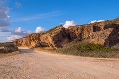 Malerische alte Felsen nahe einem Schotterweg entlang der Küste Stockfotografie