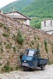 Malerische alte Gasse mit Wohnungen und ein altes italienisches Fahrzeug äffen Piaggio nach Stockbilder