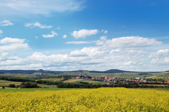 Malerische Ansicht des hügeligen Landschaftsbereichs mit Rapssamenfeld Stockfotografie