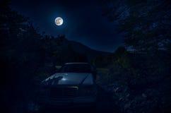 Malerische Nachtlandschaft des tiefen blauen Himmels mit dem hellen Mond, der über Auto und Bäumen beleuchtet Stockbild