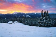 Malerische Winterlandschaft mit Hütten, schneebedeckte Berge lizenzfreie stockfotografie