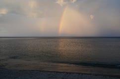 Malerischer Abendhimmel mit einem Regenbogen über dem dunklen Baikal-Wasser Lizenzfreies Stockfoto