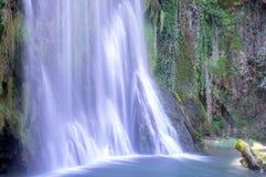 Malerischer großer Wasserfall umgeben durch den grünen Wald stockbilder