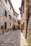 Malerischer Weg mit Blumen in einer italienischen Hügelstadt, Toskana, Stockbild