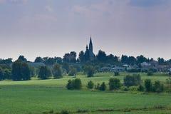 Malerisches Ackerland mit Kirche auf dem Hügel Stockfotografie