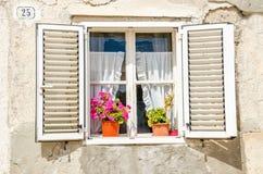 Malerisches Fenster, Fensterläden, bunte Blumen gegen eine weiße Kalksteinwand Lizenzfreie Stockfotos