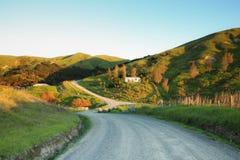 Malerisches ländliches Haus auf einem Hügel und einer Landstraße, Mahia-Halbinsel, Neuseeland Stockbilder