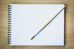Malerpinsel auf leerem Zeichenpapierbuch Stockbilder